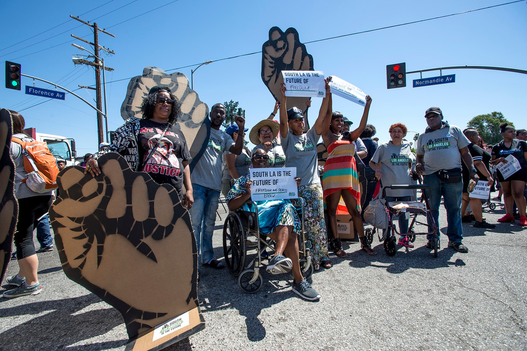 . People show their signs at the corner of W Florence Ave., and Normandie Ave., before the start of the march along W Florence Ave., and S Vermont Ave., on the 25th anniversary of the 1992 Los Angeles Riots during a march / rally and Future Fest community festival in South Los Angeles on Saturday, April 29, 2017. (Photo by Ed Crisostomo, Los Angeles Daily News/SCNG)