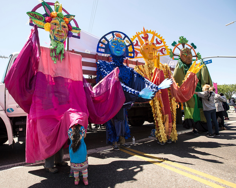 . Coyote Ayala, 4, and her friend take cover from the afternoon sunlight underneath her mother Delia Ayala\'s costume at the corner of W Florence Ave., and Normandie Ave., before the start of the march along W Florence Ave., and S Vermont Ave., on the 25th anniversary of the 1992 Los Angeles Riots during a march / rally and Future Fest community festival in South Los Angeles on Saturday, April 29, 2017. (Photo by Ed Crisostomo, Los Angeles Daily News/SCNG)
