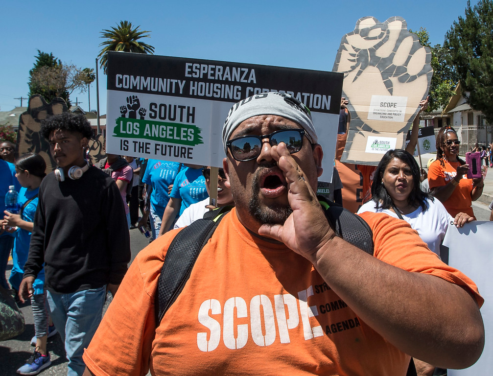 ". Andres Ramirez, center, of South Los Angeles, leads the chant ""Who\'s street Our street\"" as Hundreds of people march and chant along W Florence Ave., and S Vermont Ave., on the 25th anniversary of the 1992 Los Angeles Riots during a march / rally and Future Fest community festival in South Los Angeles on Saturday, April 29, 2017. (Photo by Ed Crisostomo, Los Angeles Daily News/SCNG)"