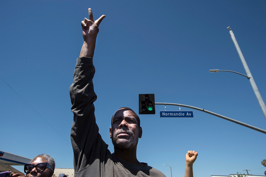 ". Edward Johnson, a resident nearby, shows a peace sign at the corner of W Florence Ave., and Normandie Ave., before the start of the march along W Florence Ave., and S Vermont Ave., on the 25th anniversary of the 1992 Los Angeles Riots during a march / rally and Future Fest community festival in South Los Angeles on Saturday, April 29, 2017. Johnson says he was there during the riots and didn\'t loot. ""The world needs more peace\"" he said.  (Photo by Ed Crisostomo, Los Angeles Daily News/SCNG)"