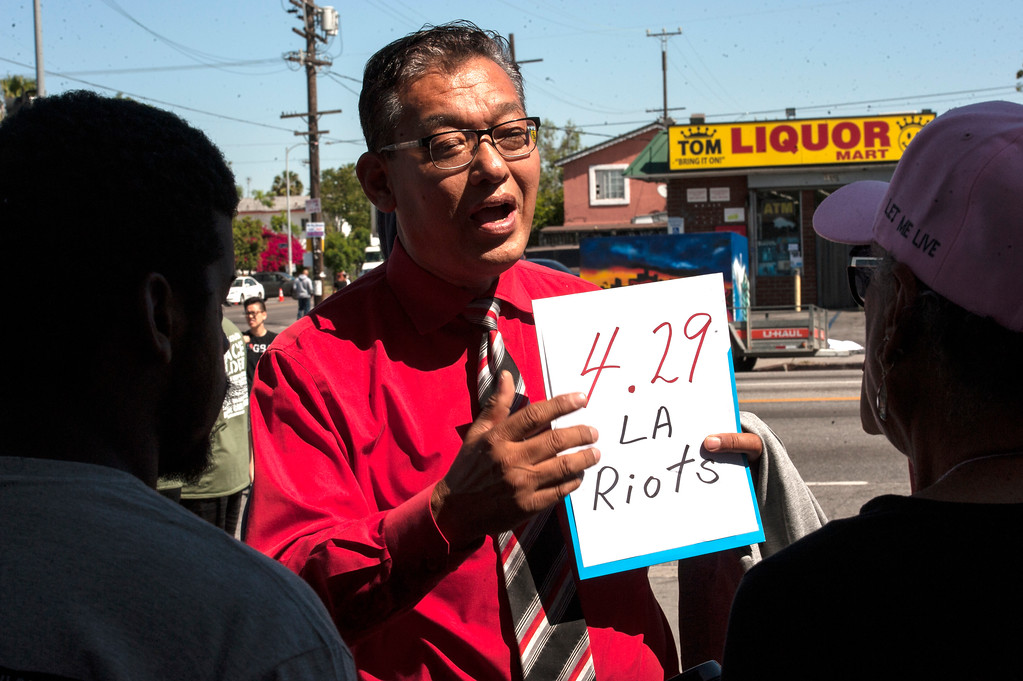. Pastor Timothy Kwan-Ung Park shows a sign at the corner of W Florence Ave., and Normandie Ave., before the start of the march along W Florence Ave., and S Vermont Ave., on the 25th anniversary of the 1992 Los Angeles Riots during a march / rally and Future Fest community festival in South Los Angeles on Saturday, April 29, 2017. He says his business on W Pico Blvd., was not damage during the LA riots, but other business across the street were burnt and damaged. (Photo by Ed Crisostomo, Los Angeles Daily News/SCNG)