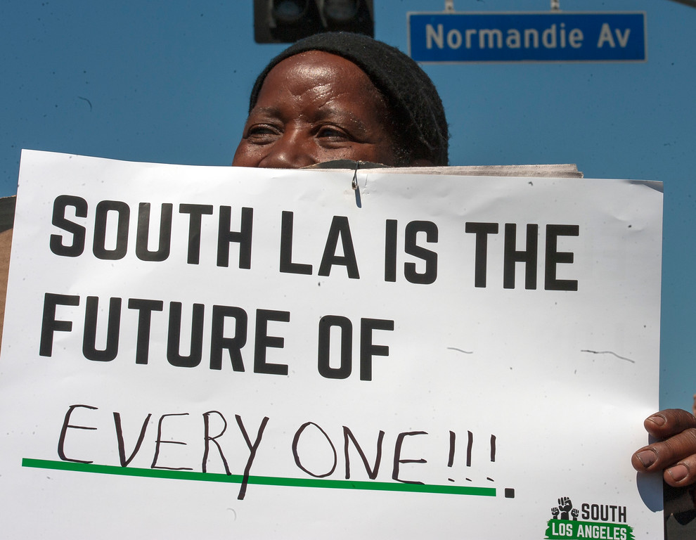 . Mavis Higgenbotham shows a sign at the corner of W Florence Ave., and Normandie Ave., before the start of the march along W Florence Ave., and S Vermont Ave., on the 25th anniversary of the 1992 Los Angeles Riots during a march / rally and Future Fest community festival in South Los Angeles on Saturday, April 29, 2017. (Photo by Ed Crisostomo, Los Angeles Daily News/SCNG)