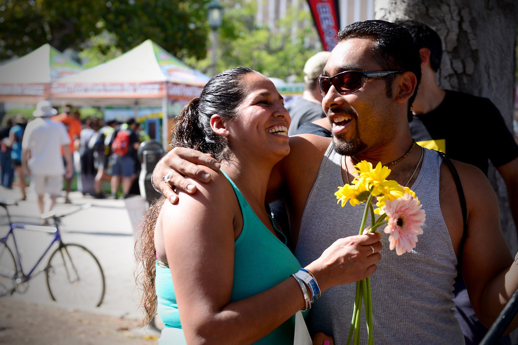 ". Jonathan Wolff, of Highland Park, gives his girlfriend Veronica RIvera flowers that Kind bars was handing out with their campaign ""pick one and pass it on\"" during the Amgen Tour of California in Pasadena Saturday, May 17, 2014. (Photo by Sarah Reingewirtz/Pasadena Star-News)"