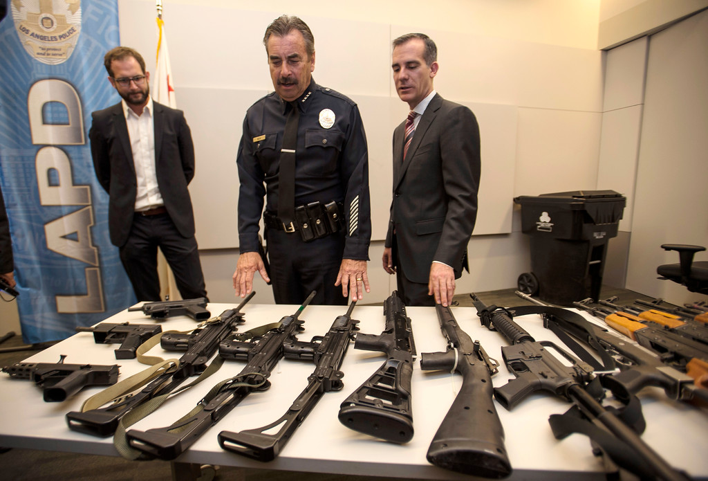 . LAPD Chief Charlie Beck, center, shows assault rifles and pistols from the San Fernando Valley surrendered anonymously as Los Angeles Mayor Eric Garcetti and Ian Johnstone, left, co-founder of gunbygun, look on after a press conference announcing the results for the anonymous gun buyback at Los Angeles Police Department Headquarters in Los Angeles on Friday, May 19, 2017. (Photo by Ed Crisostomo, Los Angeles Daily News/SCNG)