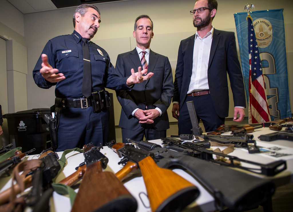 . LAPD Chief Charlie Beck, left, shows assault rifles, guns and pistols from Los Angeles surrendered anonymously as Los Angeles Mayor Eric Garcetti and Ian Johnstone, right, co-founder of gunbygun, look on after a press conference announcing the results for the anonymous gun buyback at Los Angeles Police Department Headquarters in Los Angeles on Friday, May 19, 2017. (Photo by Ed Crisostomo, Los Angeles Daily News/SCNG)