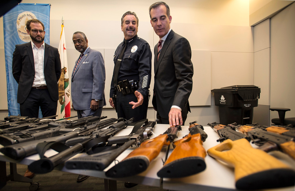 . LAPD Chief Charlie Beck shows assault rifles and pistols from the San Fernando Valley surrendered anonymously as Los Angeles Mayor Eric Garcetti, right, and Ian Johnstone, left, co-founder of gunbygun, look on after a press conference announcing the results for the anonymous gun buyback at Los Angeles Police Department Headquarters in Los Angeles on Friday, May 19, 2017. (Photo by Ed Crisostomo, Los Angeles Daily News/SCNG)