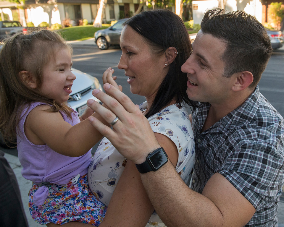 . Amanda Crihfield holds her daughter, Victoria, as her husband Brad plays with her while near their home in Bellflower June 14, 2017. At the time their two-to-three months old, Victoria, was diagnosed with some rare form of cancer and given a 10 percent chance of surviving.  After chemo, radiation etc., she will be celebrating her third birthday this Saturday, a great Father\'s Day gift. Another gift is on the way this week, Amanda is supposed to deliver another baby any day. (Photo by Thomas R. Cordova, Press-Telegram/SCNG)
