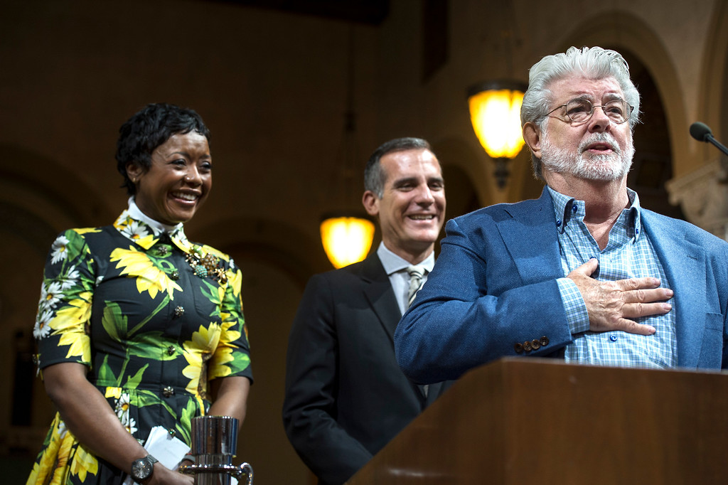 . George Lucas, right, addresses the Los Angeles City Council members as his wife Mellody Hobson, left, and Mayor Eric Garcetti look on during a meeting at City Hall in Los Angeles on Tuesday, June 27, 2017.  The City Council approved the Lucas Museum of Narrative Art project in Exposition Park. (Photo by Ed Crisostomo, Los Angeles Daily News/SCNG)