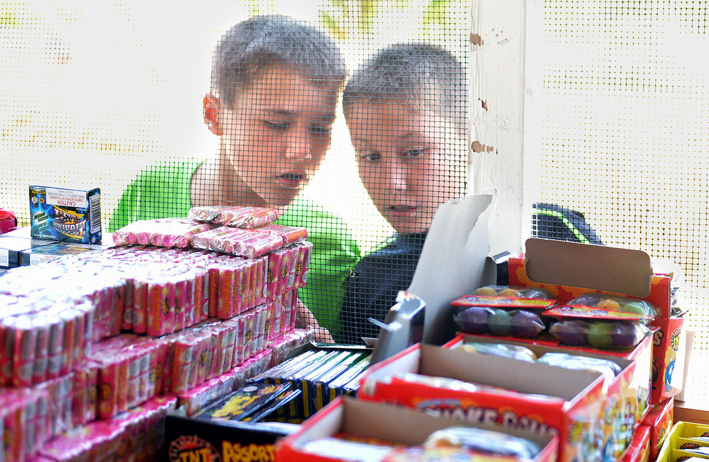 . Brothers Caleb, 8, and Joshua Robinson, 10, try to agree on what to ask for on Wednesday afternoon at the Lakewood YMCA fireworks stand. Safe and Sane fireworks are legal in Lakewood and the stands will likely be very busy the next two days.  Long Beach July 2, 2014.  (Photo by Brittany Murray / Daily Breeze)