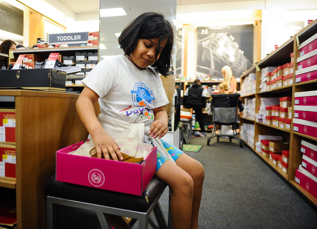 . Rosa Zaragoza, 7, tries on new shoes during a Boys & Girls Club back-to-school $100 shopping spree at Kohl\'s in Redlands, Calif. on Saturday, Aug. 5, 2017. Local nonprofits and community leaders escorted 122 Boys & Girls Club members around Kohl\'s to help pick out clothes and accessories for the new school year. (Photo by Rachel Luna, The Sun/SCNG)