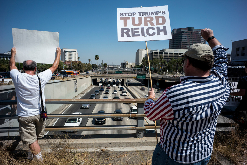 . Marchers wave signs at motorists on the 101 freeway in Los Angeles Sunday.  A rally in Los Angeles drew hundreds to stand in solidarity with Charlottesville and the death of Heather Heyer who was run over by a motorist while participating in an anti-KKK protest.  The group gathered at City Hall then marched to the Metropolitan Detention Center in downtown Los Angeles Sunday, August 13, 2017.   ( Photo by David Crane, Los Angeles Daily News/SCNG)