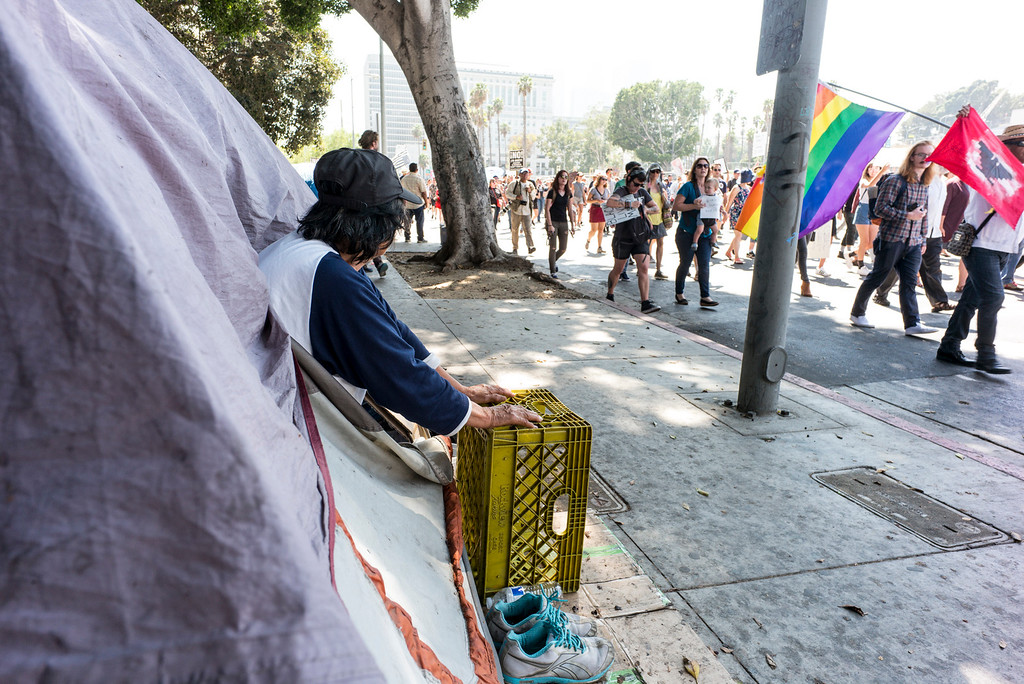 . A homeless person looks out from her tent as Marchers pass by near Olivera street in Los Angeles Sunday.  A rally in Los Angeles drew hundreds to stand in solidarity with Charlottesville and the death of Heather Heyer who was run over by a motorist while participating in an anti-KKK protest.  The group gathered at City Hall then marched to the Metropolitan Detention Center in downtown Los Angeles Sunday, August 13, 2017.   ( Photo by David Crane, Los Angeles Daily News/SCNG)
