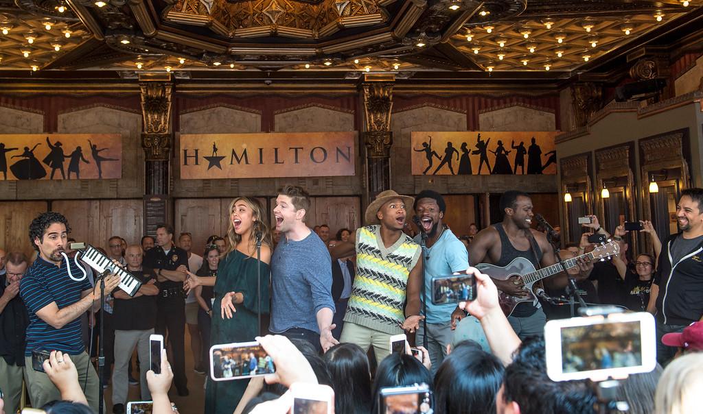 ". Surprise guests and cast members perform for fans as Lin-Manuel Miranda, right, ""Hamilton\"" creator, looks on in front of the Hollywood Pantages Theatre in Hollywood during \""Hamilton\"" ticket lottery on Wednesday, Aug 16, 2017. (Photo by Ed Crisostomo, Los Angeles Daily News/SCNG)"