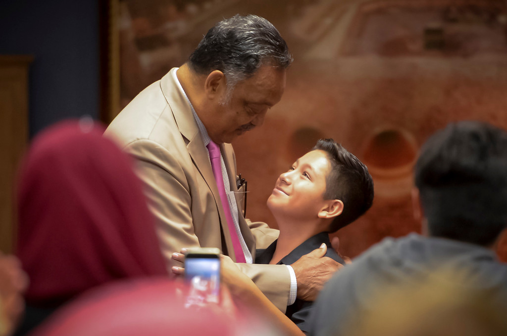 . 12-year-old Joseph Moreno gets a hug from Rev. Jesse Jackson after Moreno spoke out against racism and injustice at the Islamic Center of Southern California.   ( Photo by David Crane, Los Angeles Daily News/SCNG)