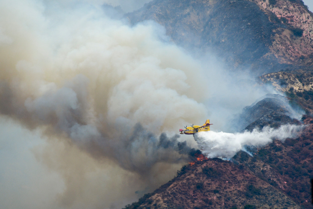 . A super scooper makes a water drop on flames on the La Tuna fire above Glendale Sunday afternoon.  The fire has destroyed 3 homes and blackened more than 5,800 acres.   ( Photo by David Crane, Los Angeles Daily News/SCNG)