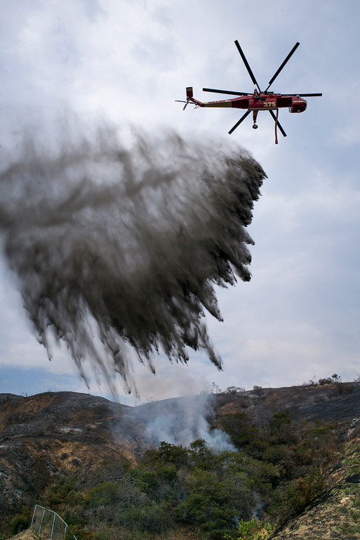. A helicopter makes a water drop on a hot spot at the end of Canter drive off of La Tuna Canyon road Sunday afternoon. The La Tuna fire has destroyed 3 homes and blackened more than 5,800 acres.   ( Photo by David Crane, Los Angeles Daily News/SCNG)