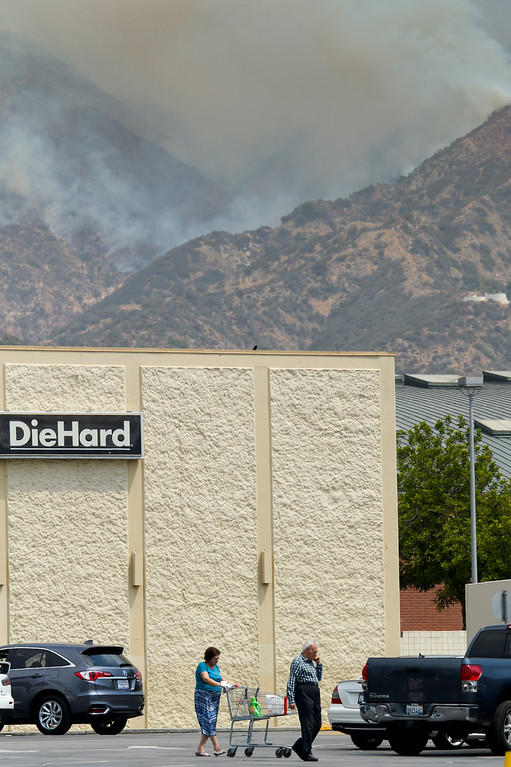 . Shoppers go about their business along San Fernando road as smoke and flames burn through the brush on the hillsides above Glendale Sunday afternoon.  The fire has destroyed 3 homes and blackened more than 5,800 acres.   ( Photo by David Crane, Los Angeles Daily News/SCNG)