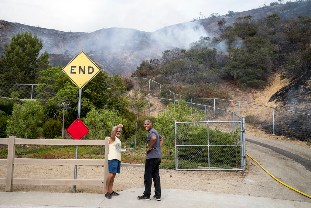 . Residents at end of Canter drive check on the fire\'s progress Sunday afternoon. The La Tuna fire has destroyed 3 homes and blackened more than 5,800 acres.   ( Photo by David Crane, Los Angeles Daily News/SCNG)