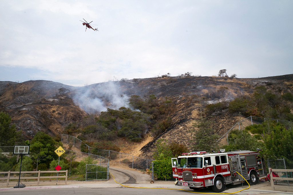 . A structure protection crew keeps an eye on flames as a helicopter circles overhead at the end of Canter drive off of La Tuna Canyon road Sunday afternoon. The La Tuna fire has destroyed 3 homes and blackened more than 5,800 acres.   ( Photo by David Crane, Los Angeles Daily News/SCNG)