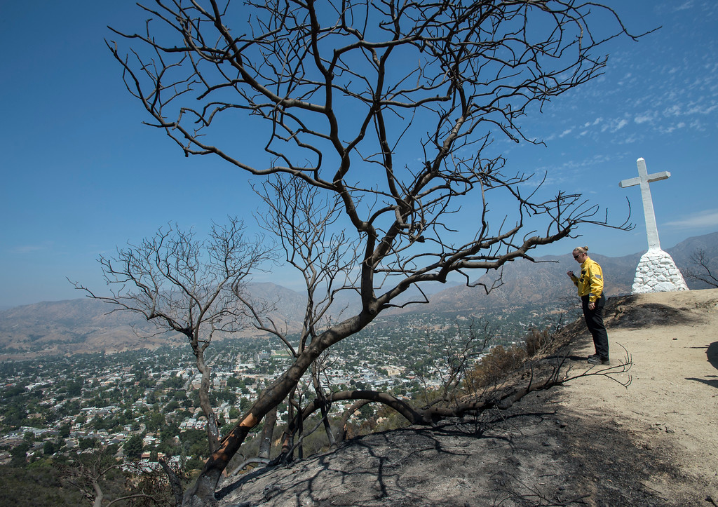 . LAFD Battalion Chief, Kady Kepner, talks with crew on her radio as she stands along Verdugo Crestline Drive with a view of Sunland Tujunga, gazes at an area where the La Tuna Fire had burn through near Tujunga on Tuesday, Sept. 5, 2017. (Photo by Ed Crisostomo, Los Angeles Daily News/SCNG)