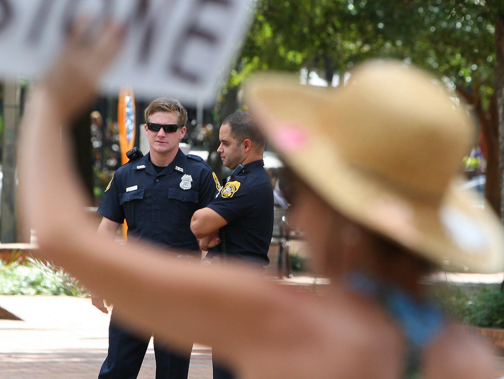 10/6/2011 TAMPA, FL - Tampa Police look on as protesters wave signs at passing vehicles  during an Occupy Tampa protest. Approximately 500 protesters came out to show support in Tampa, FL  [MANDATORY PHOTO CREDIT: LUKE JOHNSON]