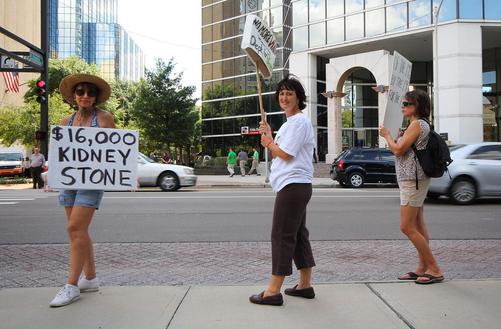 10/6/2011 TAMPA, FL - Amy Collins (Left), Denise Verrill (middle), and Linda Danaher (Right) hold up signs protesting as vehicles pass by  during an Occupy Tampa protest. Approximately 500 protesters came out to show support in Tampa, FL  [MANDATORY PHOTO CREDIT: LUKE JOHNSON]