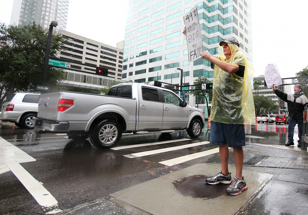 10/9/2011 TAMPA, FL - Protesters stand in the rain while holding signs during an Occupy Tampa protest in Tampa, FL. [MANDATORY PHOTO CREDIT: LUKE JOHNSON]