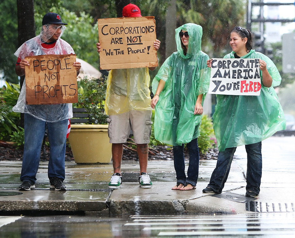 10/9/2011 TAMPA, FL - Protesters stand in the rain to wave signs at passing by vehicles during an Occupy Tampa protest in Tampa, FL. [MANDATORY PHOTO CREDIT: LUKE JOHNSON]