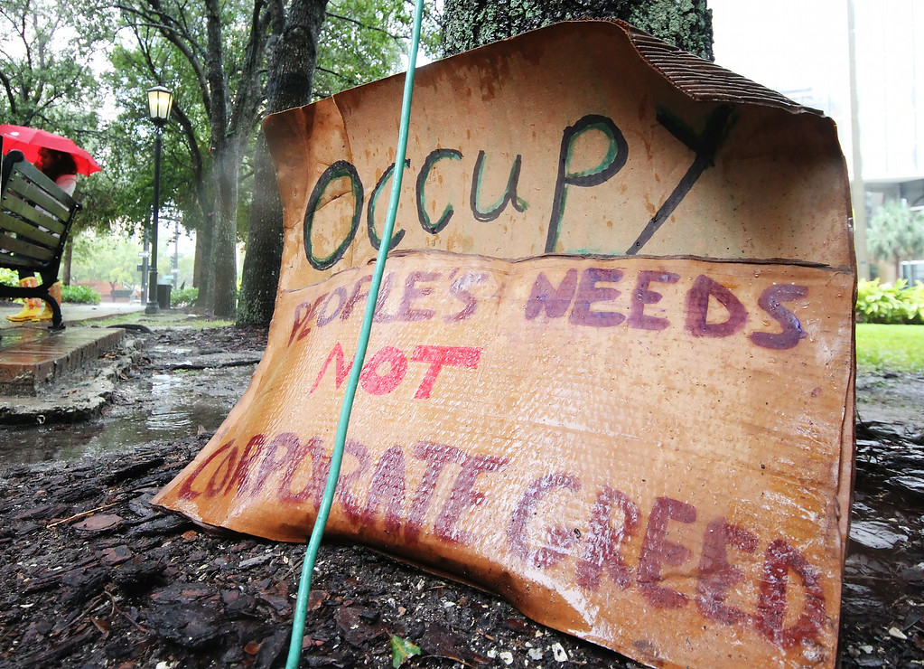 10/9/2011 TAMPA, FL - A wet sign rests against a tree during an Occupy Tampa protest in Tampa, FL. [MANDATORY PHOTO CREDIT: LUKE JOHNSON]