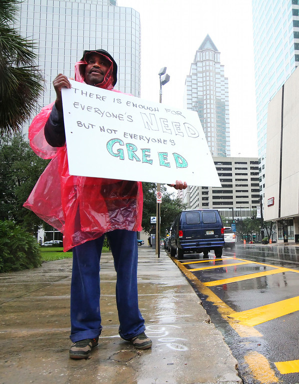 10/9/2011 TAMPA, FL - A protester stands in the rain while holding signs during an Occupy Tampa protest in Tampa, FL. [MANDATORY PHOTO CREDIT: LUKE JOHNSON]