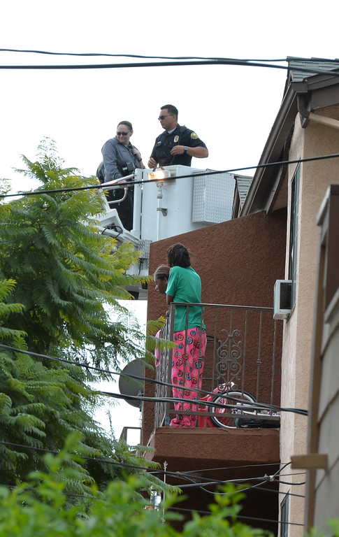 . Residents watch the scene at an apartment building in the 500 block of Nebraska Avenue where an officer involved shooting ending in the death of an unidentified suspect. The incident began with a traffic stop in the area of Walnut Avenue and 3rd Street around 2:30 a.m. followed by a foot pursuit, police said. The shooting took place on a rooftop. A Long Beach Fire Department ladder had to be used to remove the body from the roof, in Long Beach on November 19, 2013. (Photo by Brittany Murray / Press Telegram)