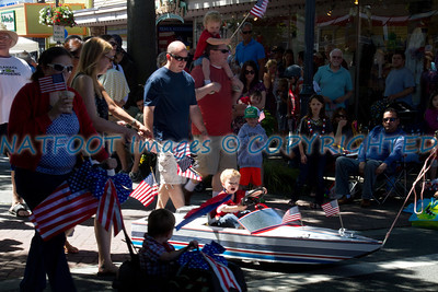 Someone is powering down the parade route with a little help from mom and dad.