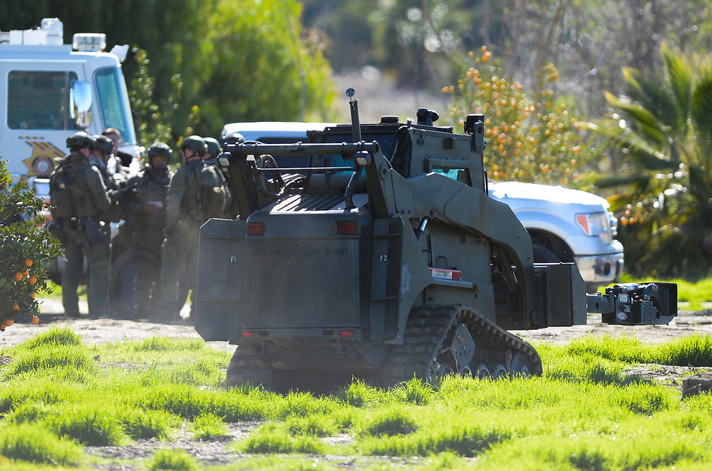 . SWAT gathers at the command post where authorities say a parolee-at-large arm himself with a long gun and then barricaded himself in a home in Loma Linda, Calif. on Wednesday, Dec. 28, 2016. Nearby homes were evacuated, and a local roadway was closed. (Photo by Rachel Luna/Redlands Daily Facts, SCNG)