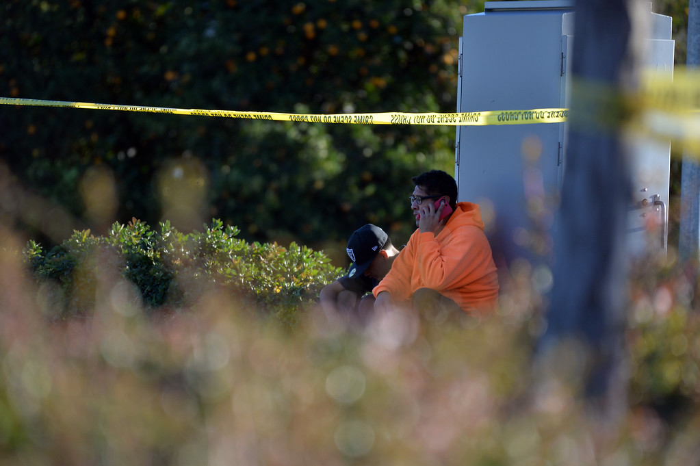 . Vince Castillo, in orange, makes a phone call as authorities work a barricade situation in Loma Linda, Calif. on Wednesday, Dec. 28, 2016. Castillo said the suspect was his nephew, who later peacefully surrendered. (Micah Escamilla/Redlands Daily Facts, SCNG)