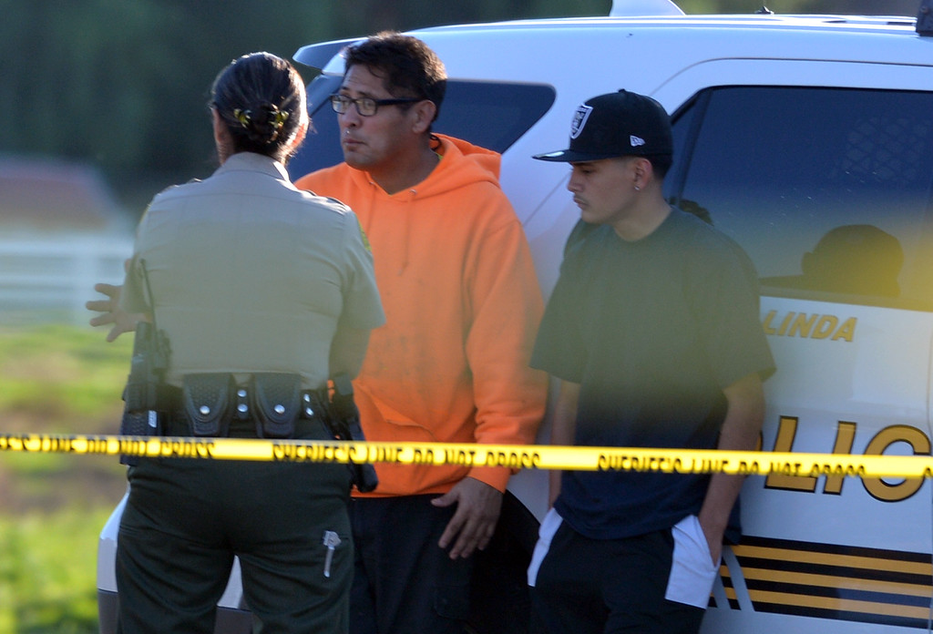 . Vince Castillo, in orange, talks to an officer during a barricade situation in Loma Linda, Calif. on Wednesday, Dec. 28, 2016. Castillo said the suspect was his nephew, who later peacefully surrendered. (Micah Escamilla/Redlands Daily Facts, SCNG)
