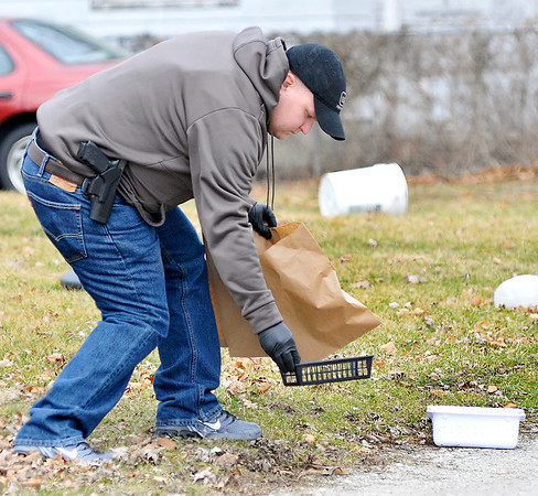 John P. Cleary    The Herald Bulletin<br /> Elwood police bag evidence from an armed robbery at Low Cost Prescriptions that was found in a alley a block west of the pharmacy.
