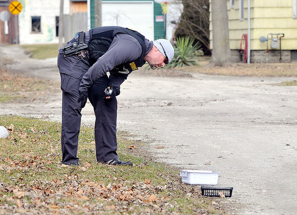 John P. Cleary |  The Herald Bulletin<br /> A Sheriff's deputy looks over evidence that was found in an alley a block west of Low Cost Prescriptions in Elwood after an armed robbery Wednesday.