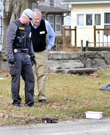 John P. Cleary    The Herald Bulletin<br /> The Elwood Low Cost Prescriptions pharmacist identifies items for a Sheriff's deputy that were taken from the store in a armed robbery Wednesday morning. The evidence were found in an alley a block west of the pharmacy.