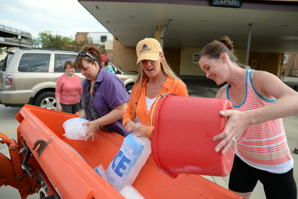 """First Federal Savings Bank staff, from left, Emily Nelson, Melanie Hium, and Brandy Johnson fill a Kubota tractor bucket with ice Wednesday evening at the downtown Sheridan First Federal Savings Bank drive through location. Several employees of the bank took the ALS Ice Bucket Challenge this week when their Senior Vice President Kay Roush challenged her coworkers after taking the challenge herself earlier this week. The members of the bank also honored their late coworker Margaret Gibson, who died last may from ALS. The #alsicebucketchallenge has become a social media phenomenon for spreading awareness about Amyotrophic lateral sclerosis, also known as """"Lou Gehrig's Disease,"""" and to raise support for the ALS Association. Those who have been challenged have 24 hours to either accept and dump ice water over their heads and challenge three other people, or donate to the ALS Association, or both. Those who took the challenge at First Federal Wednesday night challenged their friends and family; they also challenged all of the financial institutions in Sheridan. The Sheridan Press