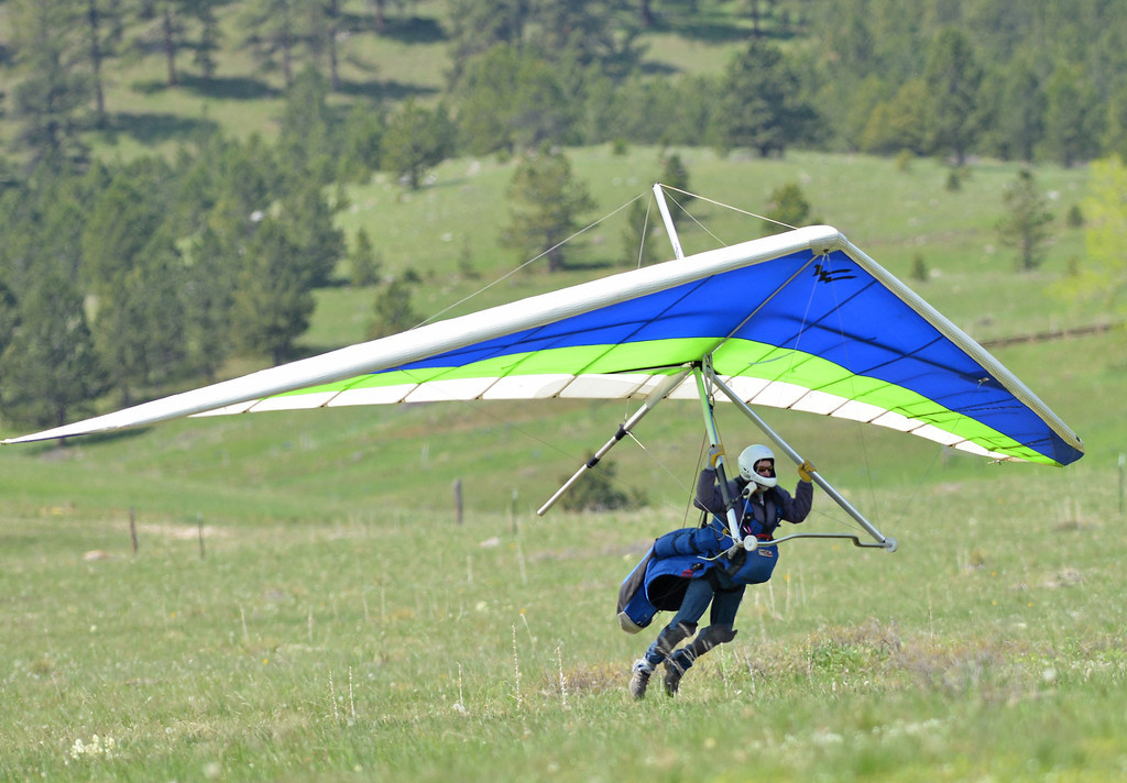 Everett Atherly of Red Lodge, Mont., brings his hang glider down on the landing zone Saturday on Highway 14 West of Dayton. Memorial Day weekend brings hang glider pilots from the region to the annual fly-in at sand turn in the Bighorn Mountains. Sand turn is known among hang glider and paraglider enthusiasts for good winds and thermal updrafts, which makes ideal flight conditions.