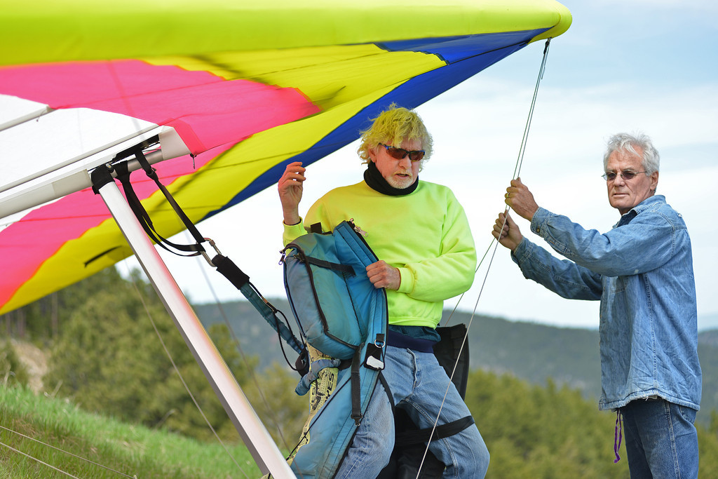 Local pilots Jim Bowman, left, puts on his gear as Johann Nield steadies the hang glider Saturday at sand turn on Highway 14 West of Dayton. Memorial Day weekend brings hang glider pilots from the region to the annual fly-in at sand turn in the Bighorn Mountains. Sand turn is known among hang glider and paraglider enthusiasts for good winds and thermal updrafts, which makes ideal flight conditions.