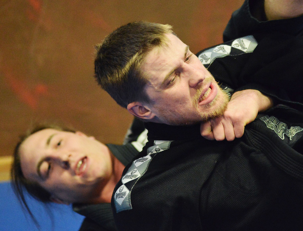 Tyler Thomas exercises a chokehold on Johnny Bublich during a practices session of Brazilian Jiu Jitsu at Harbour Combat Club Tuesday evening behind the Harbour Chiropractic Center on Broadway Street. The students at Harbour Combat Club vary in backgrounds and professions, including Emergency Medical Technicians, Lawyers, and Doctors. Some of the students take Mixed Martial Arts as professional fighters; others do it for self-defense or physical fitness.