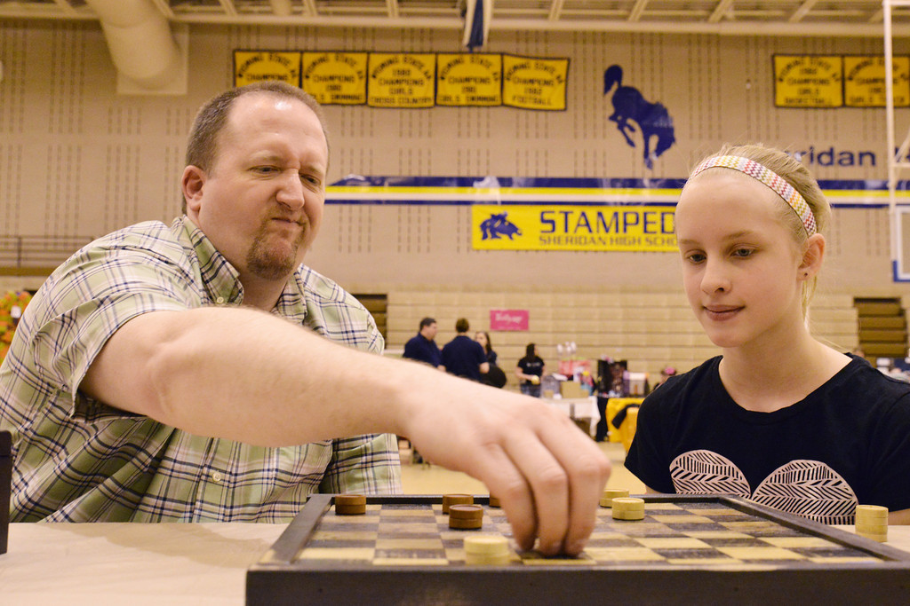Palate Creations artist Chris Yager, left, moves his piece in response to Kenzie Long in a game of checkers during the 'Get out and Shop' event Saturday at Sheridan High School. More than 50 vendors from the region came to sell goods and wares in the gymnasium.