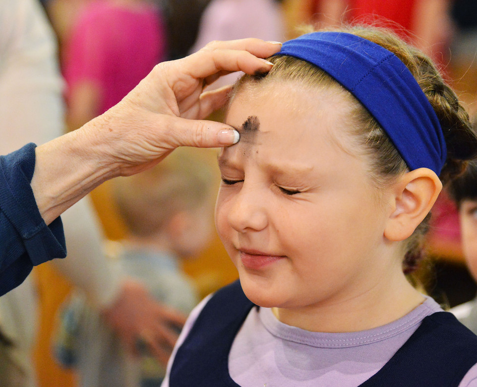 Third-grade student Robin Mercer receives an ash cross on her forehead during the Children's Service on Ash Wednesday at Holy Name Catholic Church. Ash Wednesday marks the first day of Lent leading to Easter Day.