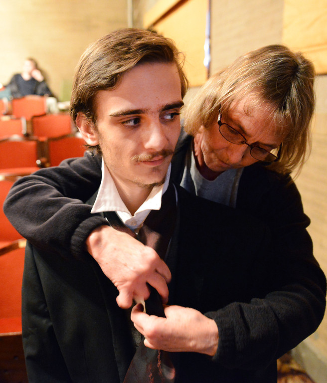 "Cindy Wiest reaches over Michael O'Kelly's shoulders to tie on a tie during a rehearsal for the Fort Mackenzie High School's ""Murder Twice Baked"" Thursday at the Carriage House Theater."