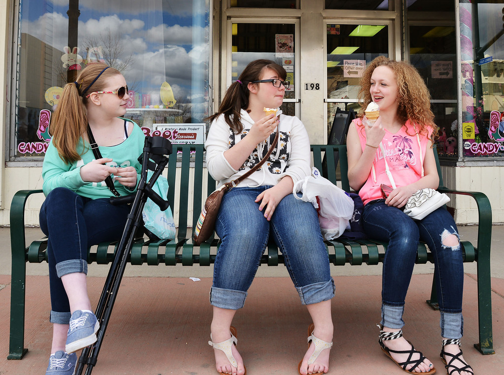 Sheridan eight graders Grace Mather, left, Cassie Johnston, and Allison Arndt sit on the bench together to enjoy some ice cream from the Sugar Boot store Saturday on Main Street.
