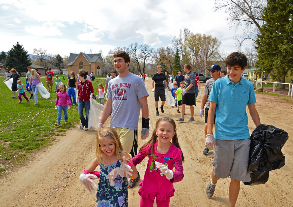 Big Horn High School students walk along with elementary students during the Earth Day clean up Tuesday in the town of Big Horn. In back, juniors Christian Mayer, left, and Jack Roberts; in front, first graders Josie Yaponcich, left, and Rachael Miller. Big Horn students from K-12 came out to pick up trash in the town of Big Horn and along the highway in celebration of Earth Day. The students collected more than 30 large bags of trash from the area. The campus also launched the next phase of their recycling program, which was initiated last year by Laurie Graves' third-grade classroom, by installing recycling bins on location. Graves says that the recycling bins are open for community use.