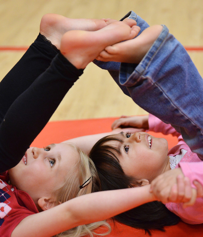 Kindergarteners Madison Thomas, left, and Kaydence Morris look up at their feet as they do a toe touch exercise during Physical Education class Tuesday afternoon at Tongue River Elementary School in Ranchester.