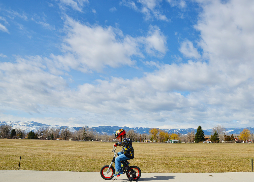 5-year-old Mason Atherton rides his bike ahead of his mother on the sidewalk near Meadowlark Elementary School Thursday morning.