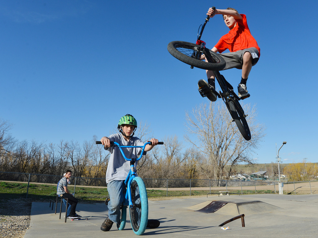 Blaine Buszkiewic sits on his bike as Jayde Wile jumps his BMX bike in front of him Thursday evening at Sheridan Skate Park. The youth have been using the Skate Park over the past month, sometimes shoveling snow and sweeping away gravel to make it safe for skateboards.